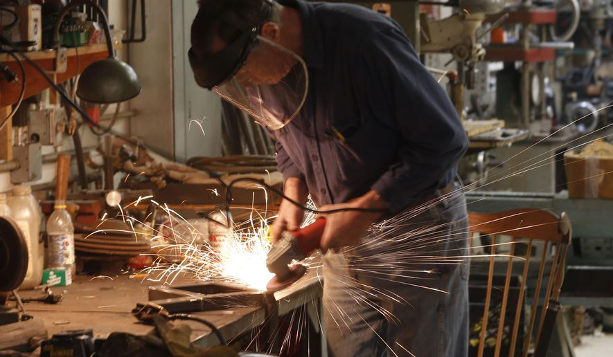 Peter Duvaloois grinds a part for a battery box for a Rat Rod he is building at his shop on Tuesday, Nov. 11, 2014, in Saugerties, N.Y. (AP Photo/Mike Groll)