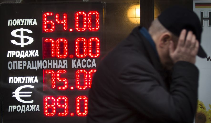 Signs advertising currencies light next to the exchange office in Moscow, Russia, Tuesday, Dec. 16, 2014. After a massive overnight rate hike by Russia's Central Bank, the ruble staged a two-hour rally Tuesday morning before rolling back to new historic lows. (AP Photo/Alexander Zemlianichenko)