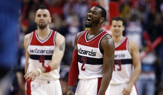 Washington Wizards guard John Wall, center, celebrates after a play with center Marcin Gortat, left, and forward Kris Humphries during the second half of an NBA basketball game against the Minnesota Timberwolves, Tuesday, Dec. 16, 2014, in Washington. The Wizards won 109-95. (AP Photo/Alex Brandon)