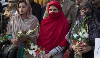 Pakistani women hold flowers to pay tribute to students of the Army Public School who were killed in an attack the day before by Taliban gunmen, as they gather outside the school in Peshawar, Pakistan, Wednesday, Dec. 17, 2014. Pakistan mourned as the nation prepares for mass funerals Wednesday for over 140 people, most of them children, killed in the Taliban massacre in the military-run school in the country's northwest in the deadliest and most horrific attacks in years, officials said. (AP Photo/B.K. Bangash)