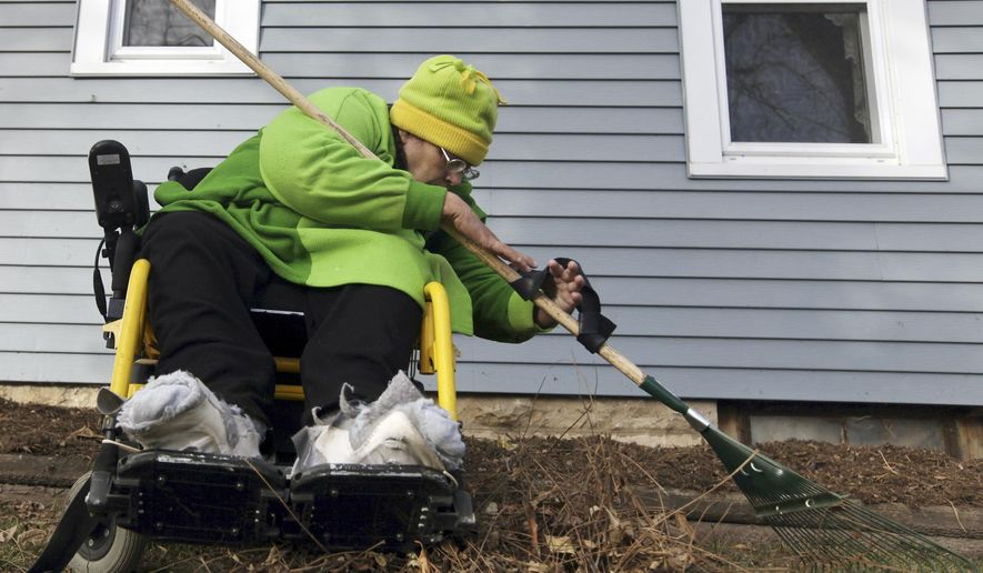 In this Oct. 29, 2014 photo, Jody Bogue rakes her yard recently at her home near Quincy, Ill. Bogue is a quadraplegic because of a February 1991 DUI-related wreck that happened on U.S. 24 near West Quincy, Mo. Using a strap made from a tire inner tube attached to the rake handle, Bogue, who is also a master gardener, commonly rakes a one and a half acre area.  (AP Photo/The Quincy Herald-Whig, Steve Bohnstedt)