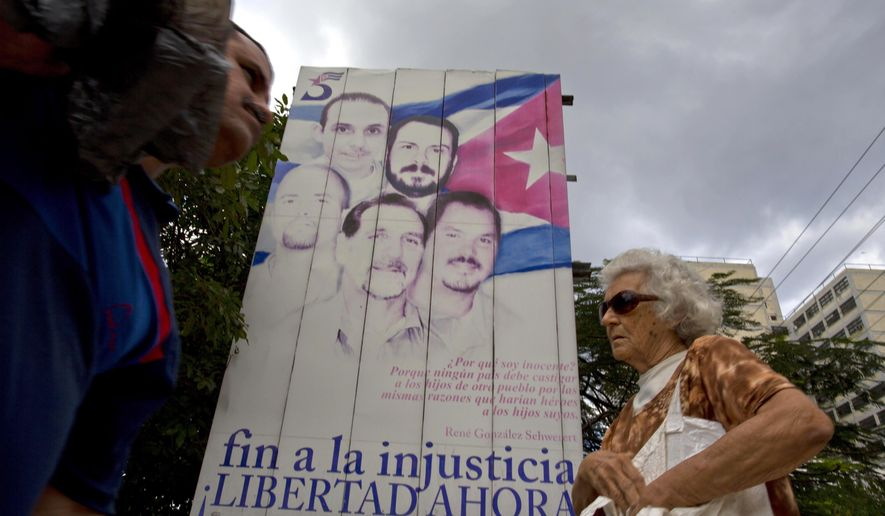 "People walk past a billboard showing ""The Cuban Five"" that reads in Spanish ""End the injustice. Freedom now."" in Havana, Cuba, Wednesday, Dec. 17, 2014. The men, who are hailed as heroes in Cuba, were convicted in 2001 in Miami on charges including conspiracy and failure to register as foreign agents in the U.S. On Wednesday, Dec. 17, 2014, three of the five Cubans were released by the U.S. in exchange for U.S. citizen Alan Gross and an unnamed Cuban man who was imprisoned for nearly 20 years for spying for the United States. Two of the Cuban Five had previously been released after finishing their sentences. (AP Photo/Desmond Boylan)"