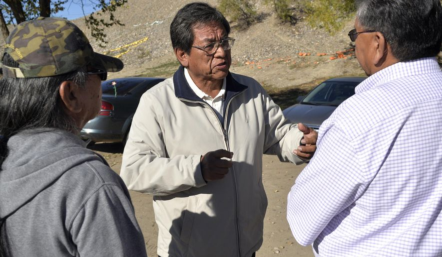 FILE - In this Nov. 4, 2014, file photo, Navajo Nation presidential candidate Russell Begaye, center, speaks with a group during the Navajo Nation elections outside of the Shiprock Chapter House in Shiprock, N.M. A ruling by the Navajo Nation Supreme Court on Wednesday, Dec. 17, 2014, clears the way for election officials to set a date for the presidential contest. The high court upheld the dismissal of a challenge against Begaye, who will face Joe Shirley Jr. for the tribe's top elected post. (AP Photo/The Daily Times, Alexa Rogals, File)