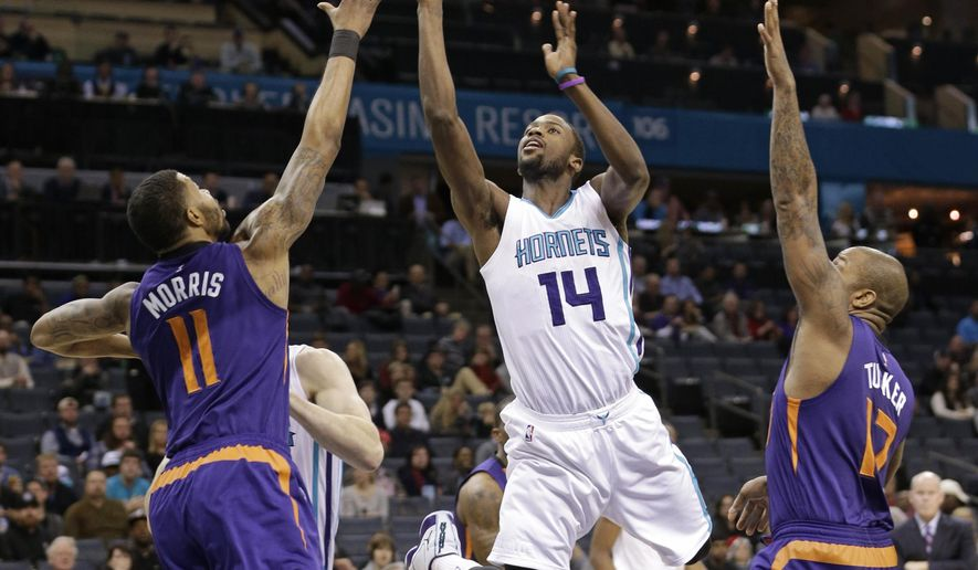 Charlotte Hornets' Michael Kidd-Gilchrist (14) shoots between Phoenix Suns' Markieff Morris (11) and P.J. Tucker (17) during the first half of an NBA basketball game in Charlotte, N.C., Wednesday, Dec. 17, 2014. (AP Photo/Chuck Burton)
