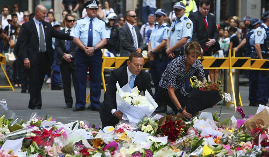 Australian Prime Minister Tony Abbott and his wife Margie pay their respect to the victims of the siege in Martin Place in Sydney central business district, Australia. Tuesday, Dec. 16, 2014. Abbott has laid flowers at a makeshift memorial in Sydney for the victims of a central city cafe siege which left three people dead. (Photo: Steve Christo)