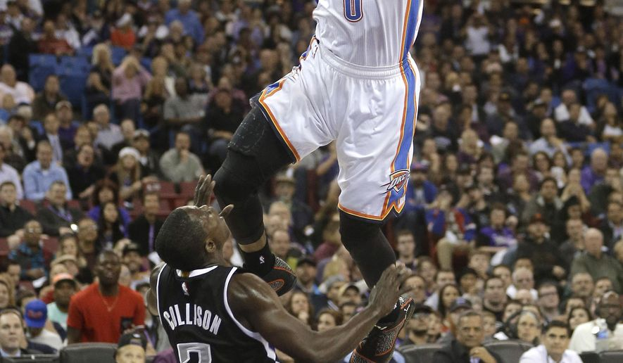 Oklahoma City Thunder guard Russell Westbrook, top, is fouled by Sacramento Kings guard Darren Collison during the first quarter of an NBA basketball game in Sacramento, Calif., Tuesday, Dec. 16, 2014. (AP Photo/Rich Pedroncelli)