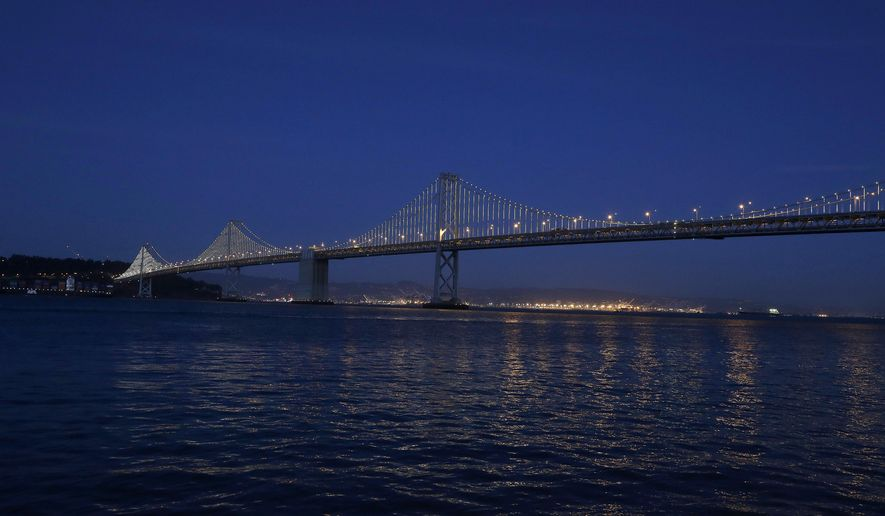 """FILE - In this Feb. 20, 2013 file photo, lights are turned on along the western half of the San Francisco-Oakland Bay Bridge, seen from San Francisco. Illuminate the Arts said Wednesday, Dec. 17, 2014, that private donations and a deal with the Bay Area Toll Authority will allow """"The Bay Lights"""" to keep shining on the bridge following an intermission of many months next year. Created by New York artist Leo Villareal, """"The Bay Lights"""" consists of 25,000 white lights spaced a foot apart on the span's vertical cables and individually programmed to produce sequences of shifting light. (AP Photo/Jeff Chiu, File)"""