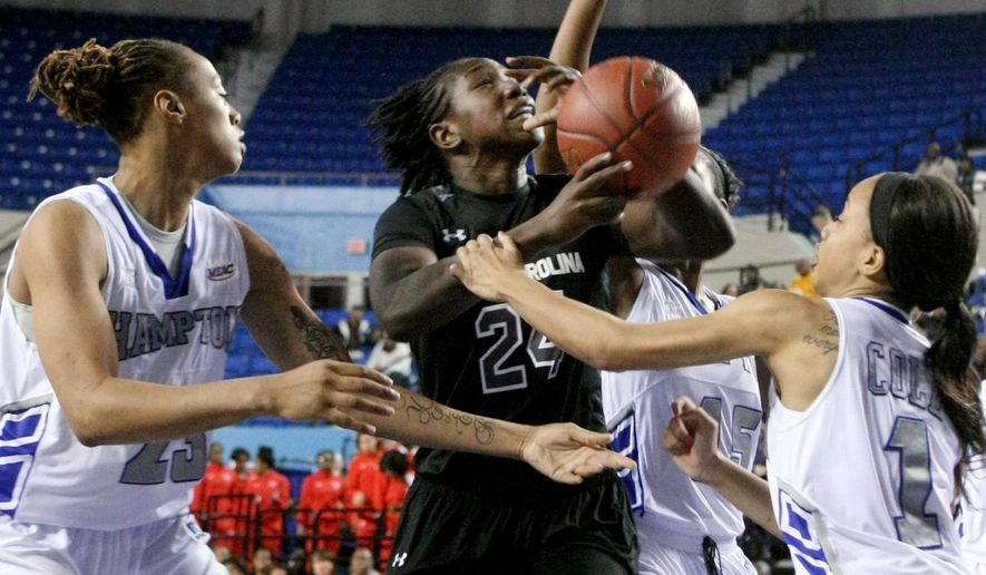 South Carolina's Aleighsa Welch, center, shoots between Hampton's Tyler Hobgood, left, and Kenia Cole, right, during the first half of an NCAA college basketball game Wednesday, Dec. 17, 2014, in Hampton, Va. (AP Photo/Jason Hirschfeld)