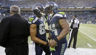 Seattle Seahawks' Doug Baldwin, center left, shakes hands as Marshawn Lynch heads off the field against the San Francisco 49ers late in the second half of an NFL football game, Sunday, Dec. 14, 2014, in Seattle. The Seahawks won 17-7. (AP Photo/Elaine Thompson)