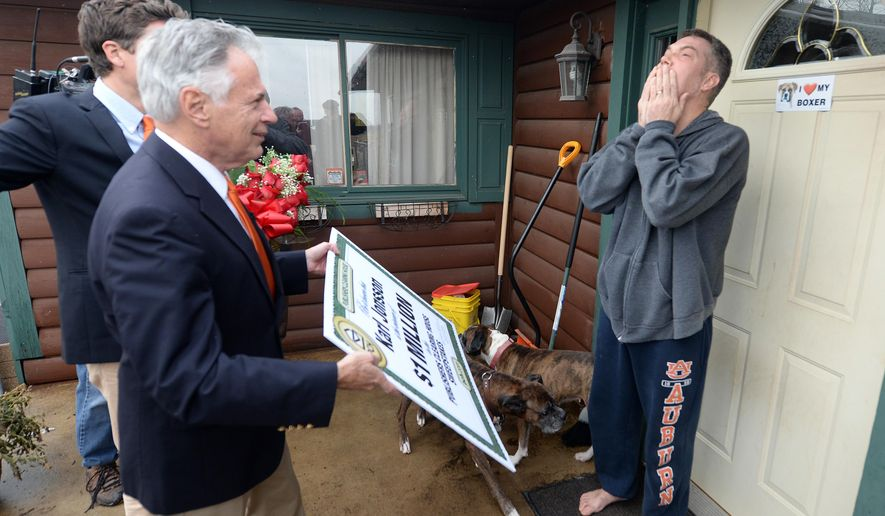 Karl Jonsson, right, reacts as Dave Sayer of the Prize Patrol, left, tells him he is the $1 million Publisher's Clearinghouse Sweepstakes winner at his home on Tuesday, Dec. 16, 2014 in Gresham, Wis. Jonsson, an electrician, has been out of work for more than three years due to a string of injuries. He plans to use the money  to pay bills. (AP Photo/The Green Bay Press-Gazette, Jim Matthews) NO SALES