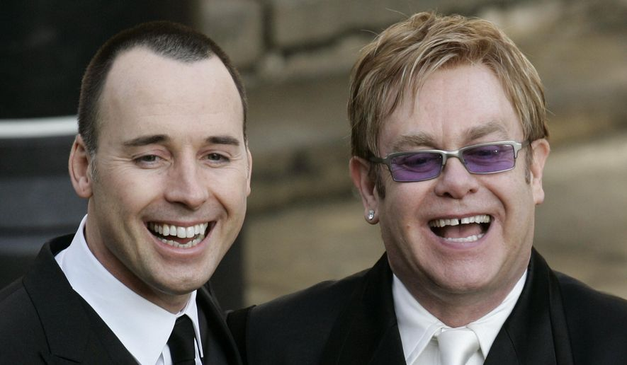 Pop star Elton John, right, and his longtime partner David Furnish, share a laugh after their civil ceremony at the Guildhall in Windsor, England on Dec. 21, 2005. (Associated Press)