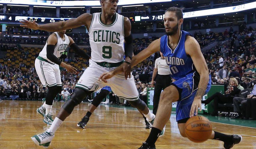 Orlando Magic guard Evan Fournier (10) drives against Boston Celtics guard Rajon Rondo (9) during the first half of an NBA basketball game in Boston, Wednesday, Dec. 17, 2014. (AP Photo/Elise Amendola)