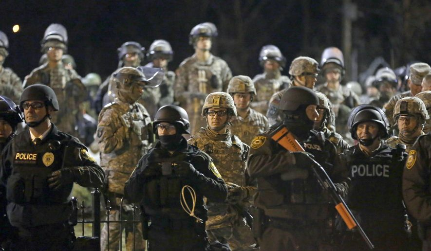 FILE - In this Nov. 28, 2014 file photo Police and Missouri National Guardsmen stand guard as protesters gather in Ferguson, Mo. Missouri Gov. Jay Nixon on Wednesday, Dec. 17, 2014 ended the state of emergency for unrest in the St. Louis area related to the grand jury announcement in the Ferguson case, lauding the efforts of police and the Missouri National Guard for preventing any loss of life.  (AP Photo/Jeff Roberson, File)