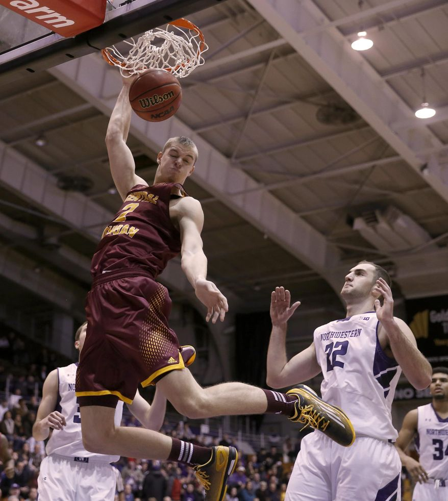 Central Michigan forward Luke Meyer, left, dunks over Northwestern center Alex Olah during the first half of an NCAA college basketball game Wednesday, Dec. 17, 2014, in Evanston, Ill. (AP Photo/Charles Rex Arbogast)