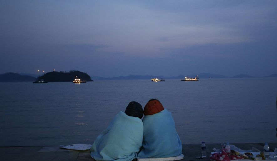 FILE - In this April 20, 2014, file photo, relatives of passengers aboard the sunken ferry Sewol sit near the sea at a port in Jindo, south of Seoul, South Korea. Over 300 people were killed in the accident, many of them students. (AP Photo/Lee Jin-man, File)