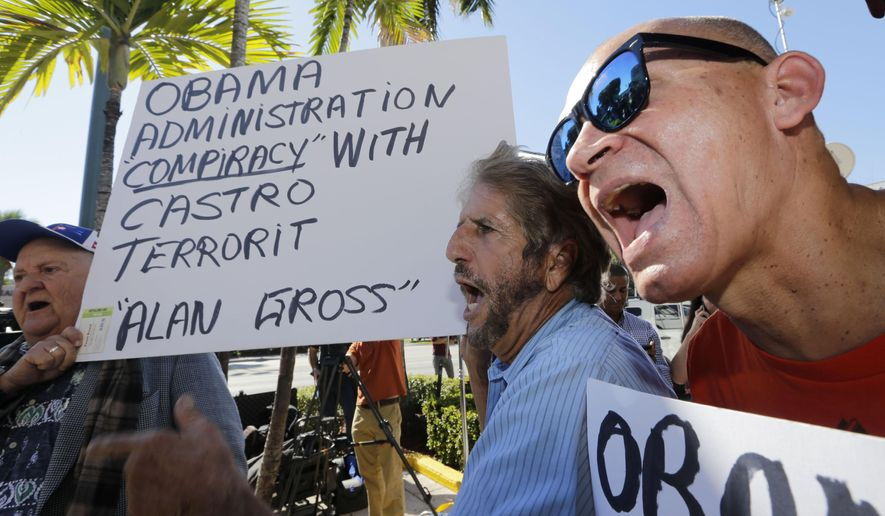 Anti-Castro activists Osvaldo Hernandez, right, and Miguel Saavedra, second from right, chant anti-Obama slogans in the Little Havana area of Miami, Wednesday, Dec. 17, 2014. Hernandez and Saavedra express their disagreement with a surprise move announced by senior Obama administration officials that could pave the way for a major shift in U.S. policy toward the communist island nation.  (AP Photo/Alan Diaz)