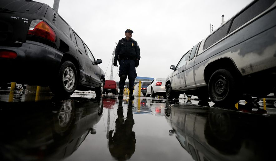 An Immigration and Customs Enforcement (ICE) agent watches cars as they wait to enter the United States from Tijuana, Mexico, through the San Ysidro port of entry in San Diego, in this Dec. 3, 2014, file photo. (AP Photo/Gregory Bull)