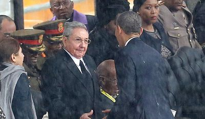 In this Tuesday Dec. 10, 2013, file photo, U.S. President Barack Obama shakes hands with Cuban President Raul Castro, as it rains during a memorial service for former South African President Nelson Mandela, at the FNB Stadium in Soweto, South Africa. (AP Photo/File) ** FILE **