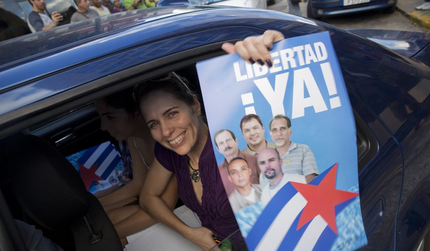 """A woman with a poster of the Cuban Five, that reads in Spanish """"Freedom Now,"""" celebrates their release, in Havana, Cuba, Wednesday, Dec. 17, 2014. After a half-century of Cold War acrimony, the United States and Cuba abruptly moved on Wednesday to restore diplomatic relations between the two nations. (AP Photo/Ramon Espinosa)"""