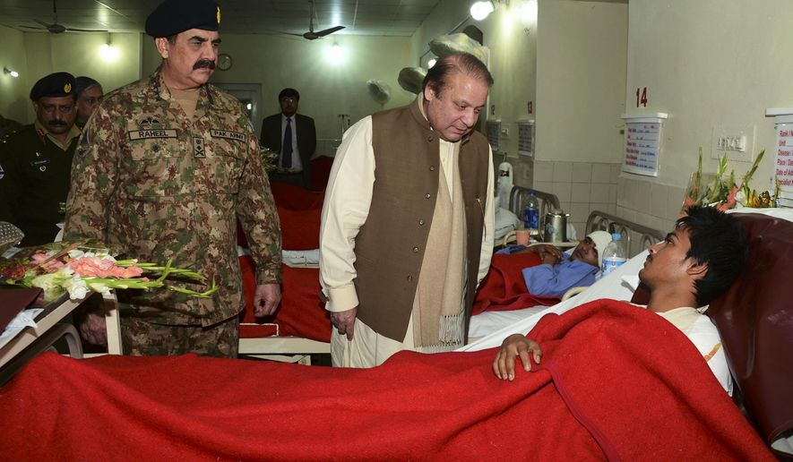 In this picture released by the Inter Services Public Relations, Pakistan's Prime Minister Nawaz Sharif, center, talks to an injured student, a victim of Tuesday's school attack, as Army Chief Gen. Raheel Sharif watches them during their visit to a military hospital in Peshawar, Pakistan, Wednesday, Dec. 17, 2014. The Taliban massacre that killed at least 148 people, mostly children, at a military-run school in northwestern Pakistan left a scene of heart-wrenching devastation, pools of blood and young lives snuffed out as the nation mourned and mass funerals for the victims got underway Wednesday. (AP Photo/Inter Services Public Relations)