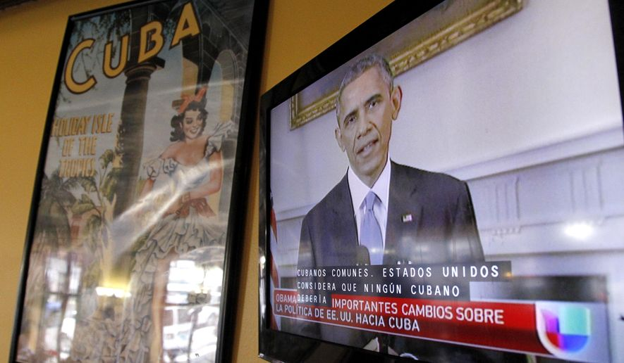 "President Barack Obama is shown on a television screen with Spanish captions as a Spanish language television network shows his speech live inside a Cuban coffee shop, Wednesday, Dec. 17, 2014, in Union City, N.J. Obama announced the re-establishment of diplomatic relations and an easing in economic and travel restrictions on Cuba Wednesday, declaring an end to America's ""outdated approach"" to the communist island in a historic shift aimed at ending a half-century of Cold War enmity. (AP Photo/Julio Cortez)"