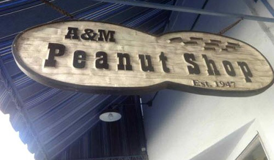 The A&M Peanut shop's sign hangs outside the store in Mobile, Ala., on Wednesday, Dec. 17, 2014. The shop's continuity and its accessibility - a half-pound of freshly roasted peanuts still costs little more than pocket change - have made it a touchstone for countless visitors. It's rare to find the place empty; and at a special event such as a recent art walk, it's not unusual to see people waiting outside on the sidewalk for other customers to depart, so that there's room for them to enter a narrow space dominated by the warmth and rustle of the ever-spinning roaster.  (AP Photo/AL.com, Lawrence Specker ) MAGS OUT