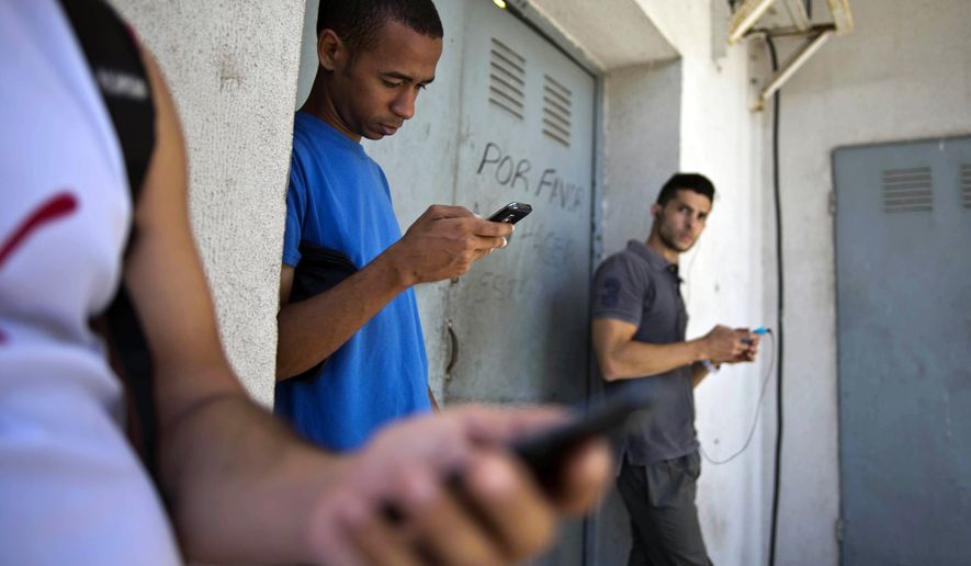 In this April 1, 2014 file photo, students stand outside a building to find an Internet signal for their phones in Havana, Cuba. (AP Photo/Ramon Espinosa, File)