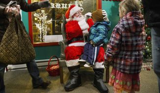 In this Dec. 10, 2014 photo, Santa Claus, portrayed by Jim Cox, prepares 2-year-old Jax Washam for his photo with his sister, Hadley, as their mother, Cara, moves in to remove his hat at the Santa House at the Old State Capitol Plaza in Springfield, Ill.  (AP Photo/The State Journal-Register, Ted Schurter)