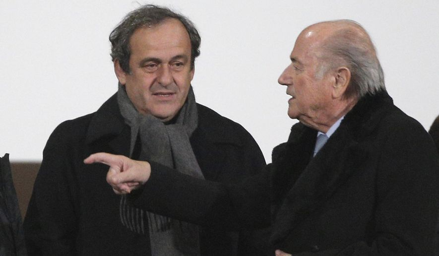 FIFA president Sepp Blatter, right, and UEFA president Michel Platini talk before the semi final soccer match between Real Madrid and Cruz Azul at the Club World Cup soccer tournament in Marrakech, Morocco, Tuesday, Dec. 16, 2014. (AP Photo/Christophe Ena)