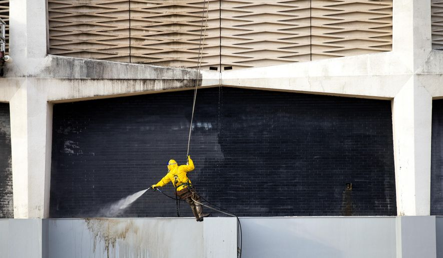 In this photo taken on Wednesday, Dec. 17, 2014, crews from Green Team Services work on cleaning the exterior of the NRG Astrodome,  in Houston. The project, which was approved by the Texas Historical Commission, requires use of an environmentally friendly cleaning agent designed to remove mold and mildew staining and is projected to be completed by January 2015, at a cost of $63,800. Proceeds from the NRG Astrodome seat sale will be used to fund the project. (AP Photo/Houston Chronicle, Brett Coomer)