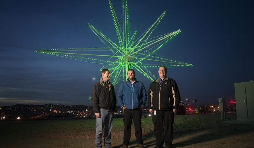 In this photo taken on Dec. 10, 2014, Gillette Electrical Superintendent Mick Wolf, left, and city electrical engineers Ry Muzzarelli, center, and Trond Birk pose for a photo in front of the Gillette star in Gillette, Wyo. The star has returned to its original home on Burma hill. It's gotten a multi-colored facelift that the three co-workers hope provide a lift for their community as well. (AP Photo/Gillette News Record, Tim Goessman) TV OUT