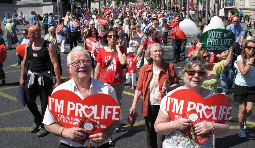 Stephen and Pauline O'Brien, foreground, holding Catholic rosary beads as they march through Ireland's capital, Dublin, in an anti-abortion protest. Ireland is debating its constitutional ban on abortion again because of a case involving a brain-dead pregnant woman on life support. Irish media reported Thursday, Dec. 18, 2014, that family members want to turn off the woman's life support systems but doctors are refusing because the law requires them to defend the right to life of her 16-week-old fetus. Fetuses typically cannot survive outside the womb until around 24 weeks. (AP Photo/Shawn Pogatchnik, File)