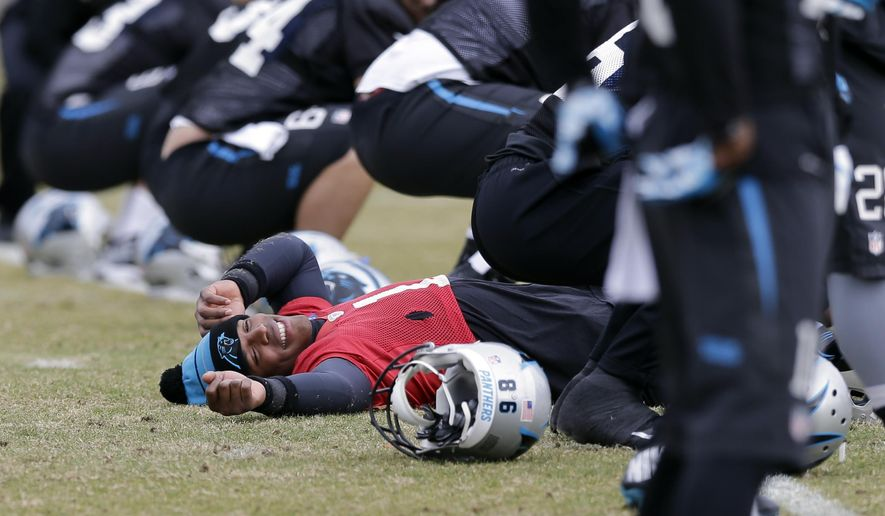 Carolina Panthers quarterback Cam Newton stretches with the team during an NFL football practice in Charlotte, N.C., Thursday, Dec. 18, 2014. (AP Photo/Chuck Burton)