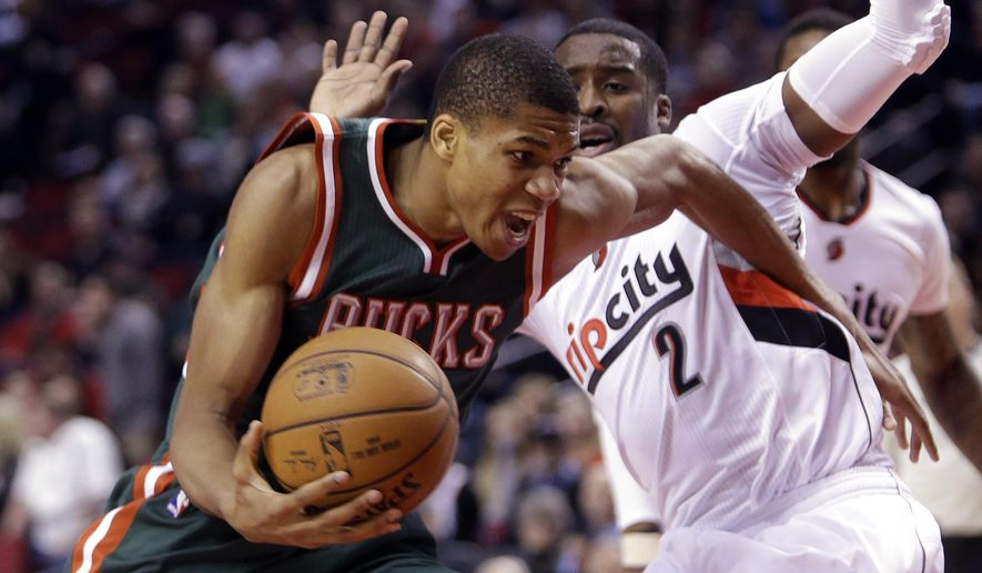 Milwaukee Bucks forward Giannis Antetokounmpo, from Greece, left, drives to the basket past Portland Trail Blazers guard Wesley Matthews during the first half of an NBA basketball game in Portland, Ore., Wednesday, Dec. 17, 2014.(AP Photo/Don Ryan)