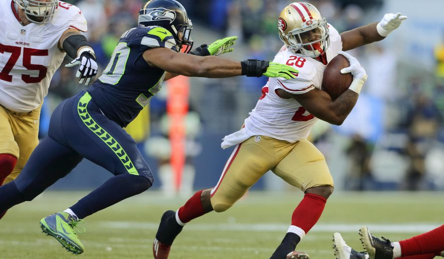 San Francisco 49ers running back Carlos Hyde (28) tries to avoid a tackle by Seattle Seahawks outside linebacker K.J. Wright, left, in the first half of an NFL football game, Sunday, Dec. 14, 2014, in Seattle. (AP Photo/John Froschauer)
