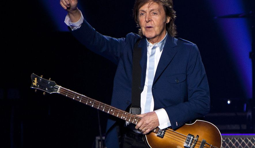 "FILE - In this Oct. 15, 2014 file photo, former Beatle Sir Paul McCartney performs in concert as part of his Out There tour at Philips Arena in Atlanta. McCartney is 72, and only the wrinkles give his years away. Interviewed recently at his midtown Manhattan office suite, he seems as boyish and graceful as he was on stage decades ago for ""The Ed Sullivan Show,"" his manner informal, his build slender and well suited for jeans and a form-fitting sweater. (Photo by Dan Harr/Invision/AP, File)"