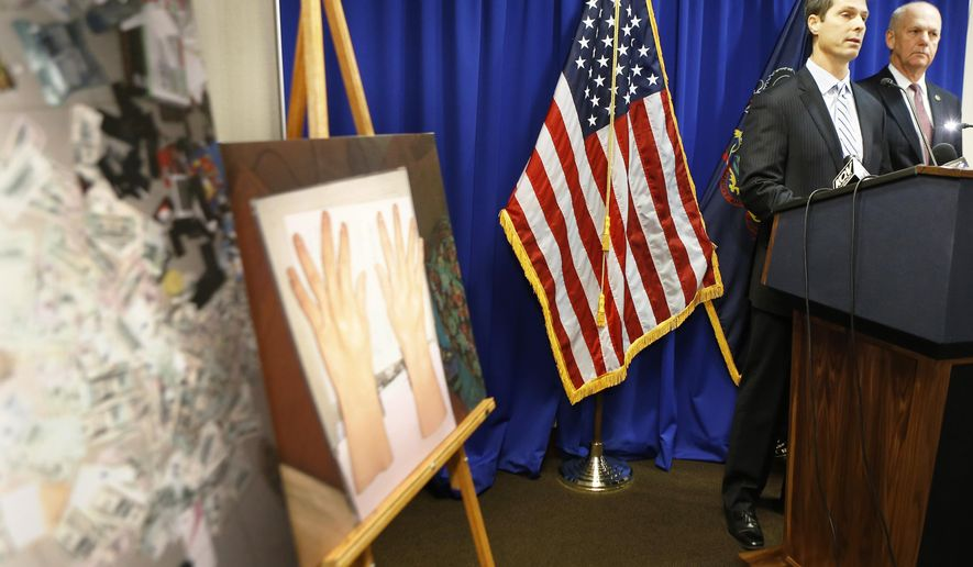 U.S. Attorney David Hickton, right, and Eric Zahren, the special agent-in-charge of Pittsburgh's U.S. Secret Service office, stand near photographs taken by the secret service in Uganda as they talk about the investigation and arrest of Ryan Andrew Gustafson, during a news conference, Thursday, Dec. 18, 2014, in Pittsburgh. Gustafson has been charged with leading an international counterfeit money operation based in the African nation of Uganda, and shipping bogus bills to the Pittsburgh area and other locations in the United States, The photo at left shows pamphlets that were allegedly used in the smuggling of the bills. The photo at left shows alleged counterfeit bills, the photo at right shows synthetic gloves allegedly used in handling and passing the bills. (AP Photo/Keith Srakocic)