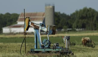 In this July 1, 2011 file photo, an oil well pumps in a pasture near Rantoul, Kan., Friday, July 1, 2011. Plunging crude prices are hitting oil producers especially hard in places like Kansas, where the industry is dominated by smaller, independent operators who depend more heavily on the cash flow from producing wells to pay for drilling new ones. (AP Photo/Orlin Wagner, File)