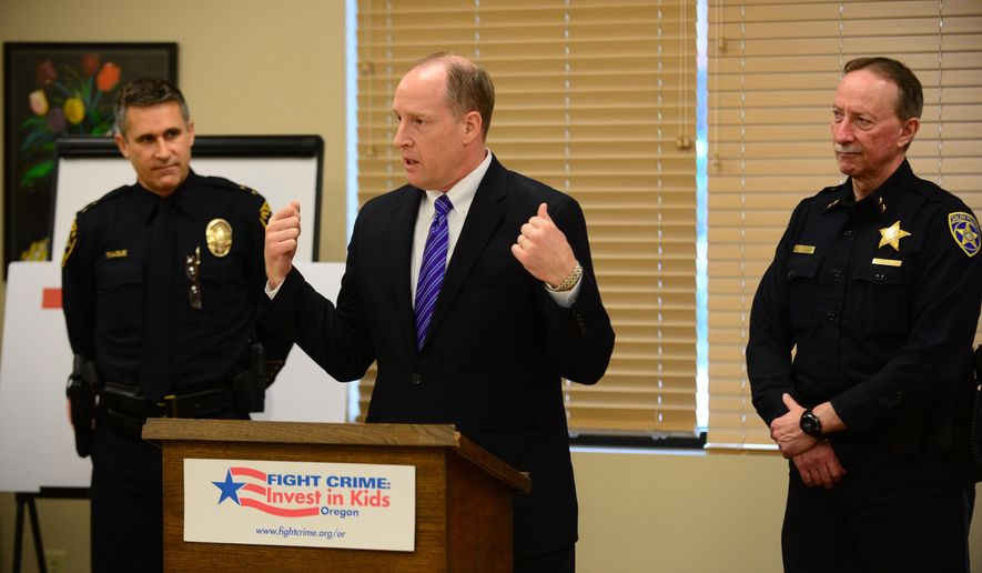 In this photo taken on Wednesday, Dec. 17, 2014, Marion County District Attorney Walt Beglau, center, speaks during a press conference at Family Building Blocks in Salem, Ore. Oregon law enforcement leaders urged the extension of the Maternal, Infant, and Early Childhood Home Visiting (MIECHV) program to reduce crime. (AP Photo/Statesman-Journal, Danielle Peterson)