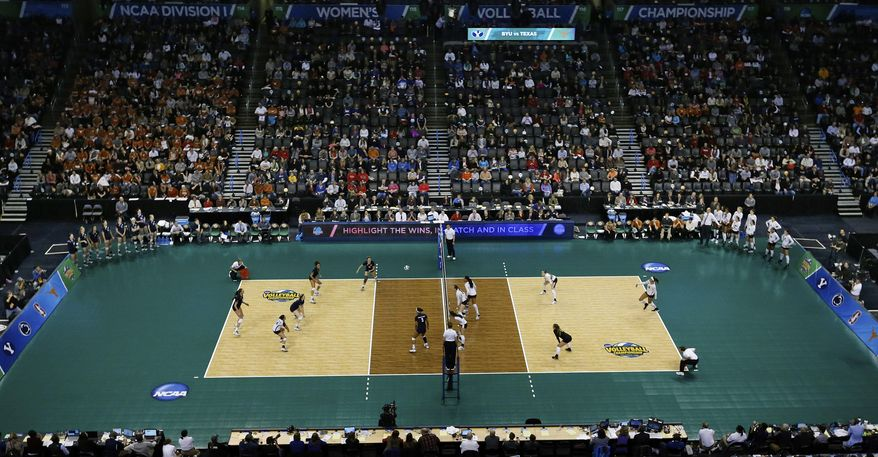 BYU, left, and Texas, right, play during an NCAA college volleyball tournament semifinal in Oklahoma City, Thursday, Dec. 18, 2014. (AP Photo/Sue Ogrocki)