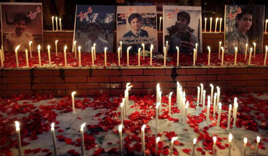 Candles are placed by local residents around portraits of the victims killed in Tuesday's Taliban attack on a military-run school in Peshawar, at a ceremony in Islamabad, Pakistan, Thursday, Dec. 18, 2014. The Taliban massacre that killed more than 140 people, mostly children, at the military-run school in northwestern Pakistan left a scene of heart-wrenching devastation, pools of blood and young lives snuffed out as the nation mourned and mass funerals for the victims got underway. (AP Photo/Anjum Naveed)