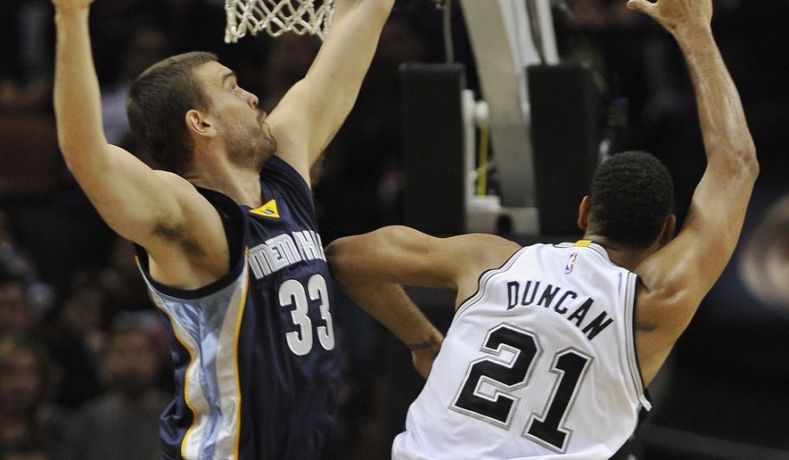 San Antonio Spurs forward Tim Duncan, right, shoots against Memphis Grizzlies center Marc Gasol, of Spain, during the first half of an NBA basketball game, Wednesday, Dec. 17, 2014, in San Antonio. (AP Photo/Darren Abate)