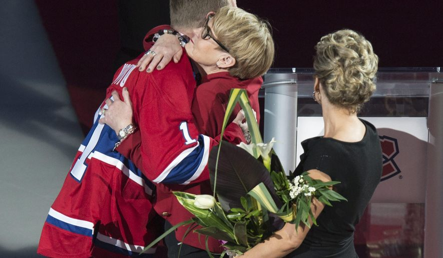 Former Montreal Canadiens captain Saku Koivu hugs his mother Tuile during a ceremony honoring his career, Thursday, Dec. 18, 2014 in Montreal.  (AP Photo/The Canadian Press, Paul Chiasson)
