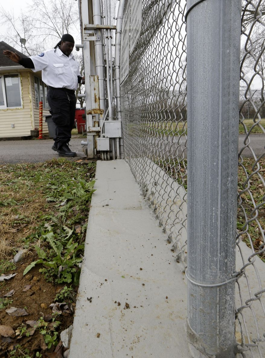 An employee passes by a concrete footing installed under the fence that surrounds the Woodland Hills Youth Development Center Thursday, Dec. 18, 2014, in Nashville, Tenn. The footing is a part of the changes that have been made to the facility following several escapes earlier this year. (AP Photo/Mark Humphrey)