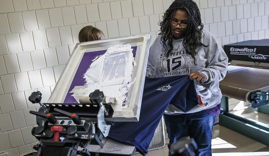 In this Nov. 14, 2014 photo, Corshia Taylor, right, a student from Southeast High School, works with Emily Hauck, a graphic designer for Ink 186, a vocational training program for students with disabilities, as they do screen printing for a batch of T-shirts for District 186's food service at the The UCP Enterprise Center, a new work force training center in Springfield, Ill. (AP Photo/The State Journal-Register, Justin L. Fowler)