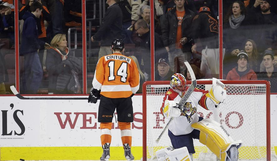 Florida Panthers' Roberto Luongo, right, celebrates after blocking a shot by Philadelphia Flyers' Sean Couturier (14) in an overtime shootout during an NHL hockey game, Thursday, Dec. 18, 2014, in Philadelphia. Florida won 2-1. (AP Photo/Matt Slocum)