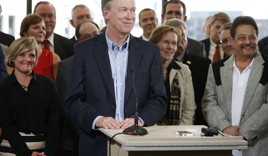FILE - In this July 17, 2014, file photo, Colorado Gov. John Hickenlooper, center, takes questions after speaking on oil and gas drilling at the Metro Denver Chamber of Commerce. As the Colorado economy improves, elected officials are getting more comfortable asking for their funding needs. But with more revenue, Colorado faces the state constitutional requirement to refund money to taxpayers, even as some lawmakers argue they haven't fully restored cuts made during the last recession. (AP Photo/Brennan Linsley, File)