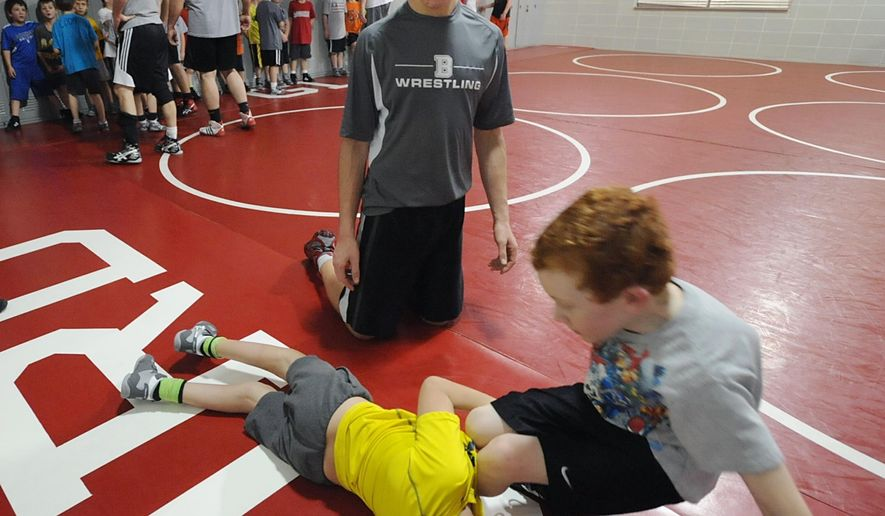 In a photo from Dec. 10, 2014, Braden Gandee, 8, left, takes down his brother Kellen, 7, as his older brother Hunter, 15, looks on during drills at the Great Lakes Wrestling Club at Bedford Junior High School in Temperance, Mich. Hunter is helping Braden, learn to wrestle months after the teen walked 40 miles with the younger boy strapped to his back.  (AP Photo/Monroe News, Tom Hawley)