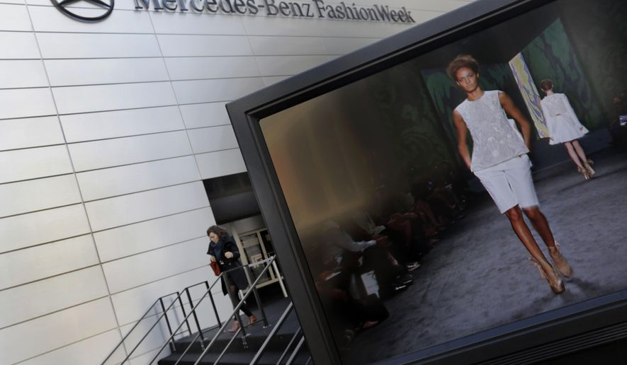 FILE - In this Feb. 6, 2013 file photo, a designer's runway show is shown on a television screen outside the Fashion Week venue at New York's Lincoln Center. The city of New York and Lincoln Center is evicting the invitation-only, twice-yearly Fashion Week in a court spat over destroyed trees and displaced park benches. (AP Photo/Richard Drew, File)