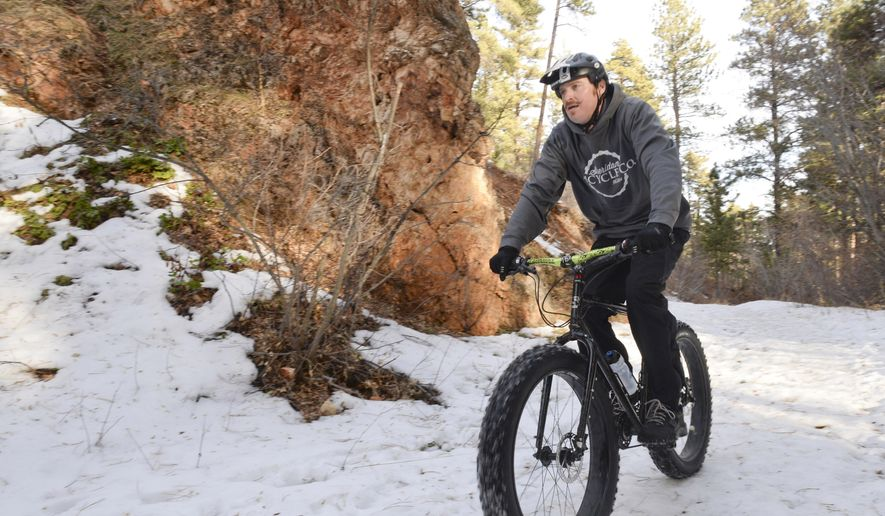 """In this photo taken on Dec. 11, 2014, Sheridan Bicycle Co. owner Jordan LeDuc rides his Surly Fat Bike on the snow down Piney Creek Trail in Story, Wyo. The bikes are designed specifically to ride in snow or sand, both of which provide little traction for regular bike tires. To combat this, bike companies developed the """"fat bike."""" (AP Photo/Sheridan Press, Justin Sheely)"""